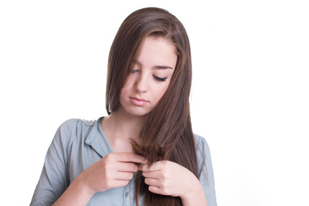 split ends: Young woman looking at split ends. Damaged long hair