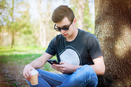 lonley: Young man sitting lonely in the park on a summers day