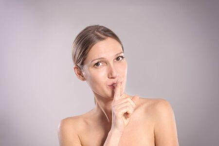 conspiratorial: Beautiful woman making a shushing gesture
