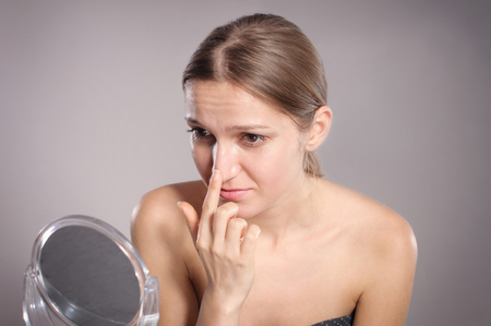 hands lifted up: Young woman checks her nose in the mirror