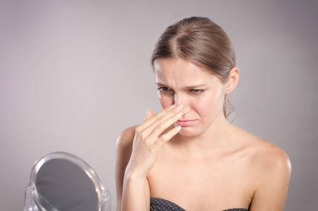 woman mirror: Young woman checks her nose in the mirror