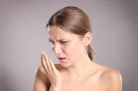 Young woman checking her breath with her hand