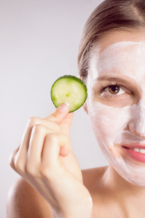 cremas faciales: Mujeres de la belleza que consigue la máscara facial Foto de archivo