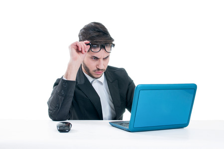 businessman working at his computer: Young business man looking at his laptop with disappointment. Isolated on white background