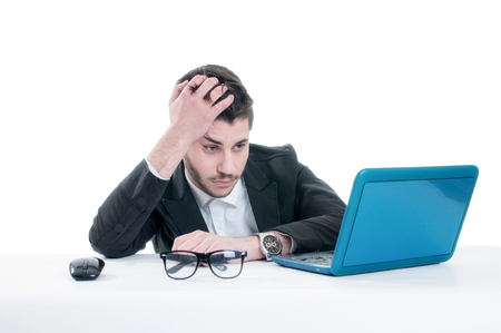 Young business man looking at his laptop with disappointment. Isolated on white background