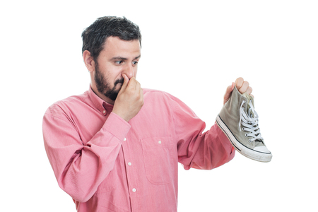 unpleasant smell: Man holding dirty stinky shoe. Unpleasant smell stink