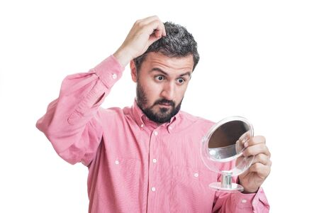 beautycare: Man worried about gray hair looking in a mirror Stock Photo