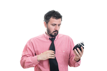 oversleep: Angry young man holding alarm clock