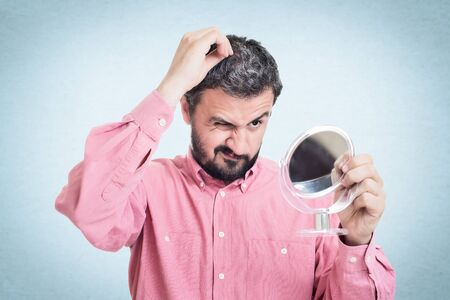 horrified: Horrified young man looking in the mirror at the first grey hair on his scalp