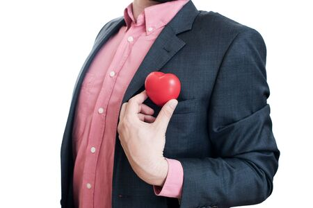 man business oriented: Man pulling out a red heart from the pocket of his suit