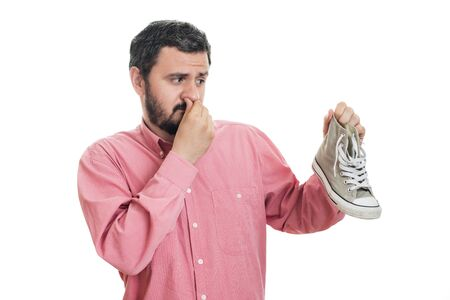 Man holding dirty stinky shoe. Unpleasant smell stink