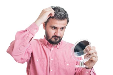 Man besorgt über graue Haare in einem Spiegel