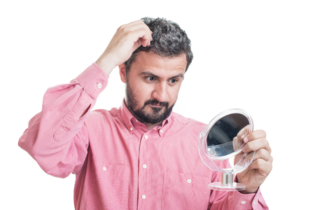 Man worried about gray hair looking in a mirror