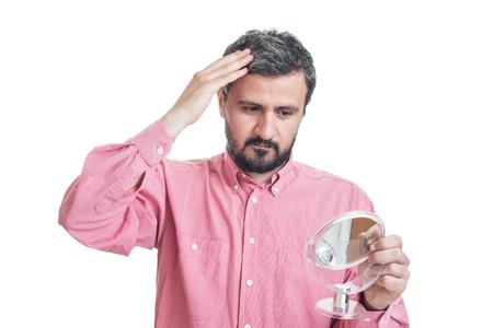 Man besorgt über graue Haare in einem Spiegel Standard-Bild