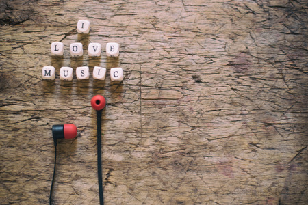unwound: Word I Love Music and earphones on wooden table
