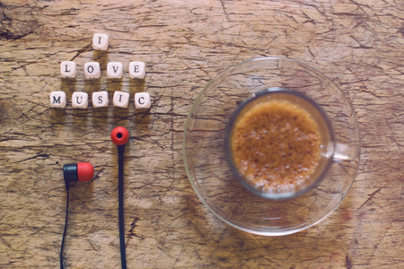 unwound: Word I Love Music, cup of coffee and earphones on wooden table Stock Photo