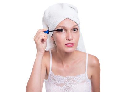 Woman applying black mascara on eyelashes with makeup brush Stock Photo