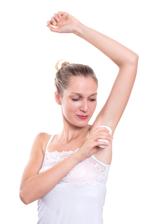Beautiful woman putting antiperspirant stick deodorant in underarms