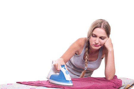 woman ironing: Bored sad young woman ironing clothes Stock Photo