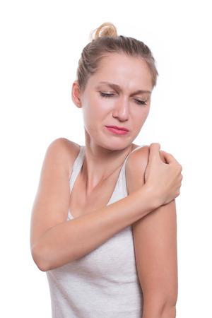 cramped: Acute pain in a woman shoulder. Female holding hand to spot of shoulder-aches