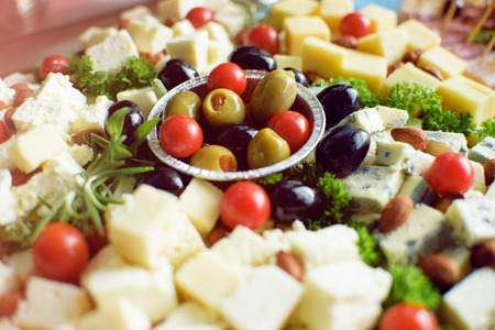 Olives, white and yellow cheese and tomato on wooden plate Stock Photo