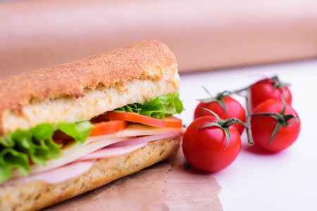 Fresh crusty baguette with ham, cheese, tomato and green salad