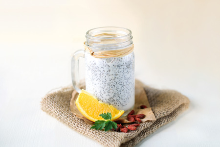 Chia seed pudding in a jar on white wooden background, decorated with orange and goji berryes