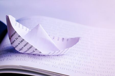 paper boat: Paper boat sails on open book