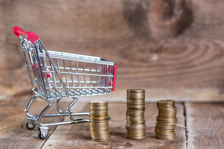 Saving and shopping concept. Coins in shopping cart
