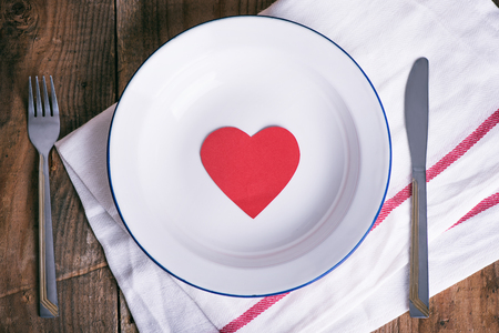 Concept diet and weight loss. Empty plate with red paper heart in the middle of the plate