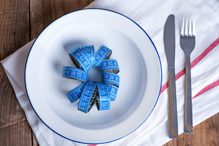 Concept diet and weight loss. Empty plate with measuring tape in the middle of the plate Фото со стока