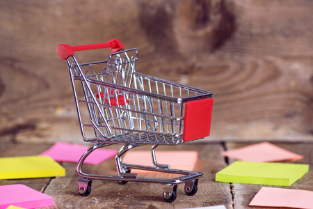 Shopping cart on wooden backround Фото со стока