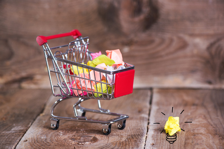Shopping cart and small paper balls. Recylcing concept with color paper and shopping cart