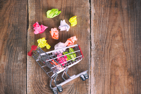 Shopping cart and small paper balls. Thinking about new idea. Ideas about e-commerce, e-commerce or commerce