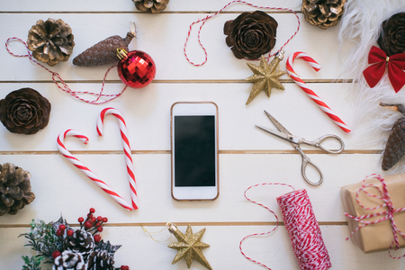 Mobile phone on wooden background with Christmas gifts. Xmas and Happy New Year composition. Flat lay, top view