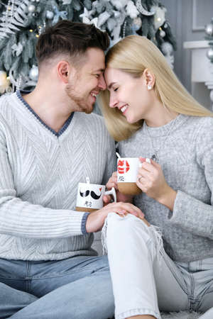 Love story of beautiful couple in studio near Christmas tree. Couple is drinking tea at the Christmas tree. Couple with cups. Girl and boy in love. Winter love story in studio. Stock Photo