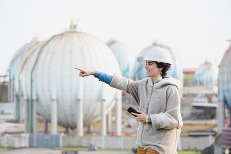 preasure: successful independent engineer smiling woman looking and pointing on industrial area with safety helmet and phone. Pioneer woman at work with spherical tanks.