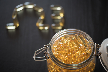 Omega 3-6-9 fish oil yellow softgels drawing omega 3 letters on wooden black table. Glass airtight jar.