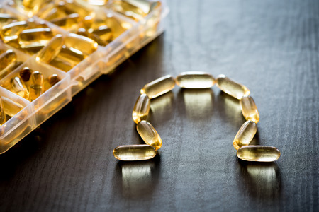 permeability: Omega 3-6-9 fish oil yellow softgels drawing omega letter on wooden black table. Daily pill box.