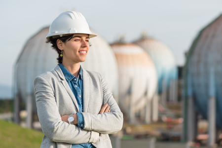 preasure: successful independent engineer smiling woman on industrial area with safety helmet crossing arms. Pioneer woman at work with spherical tanks.