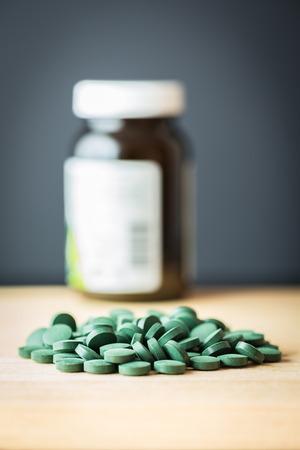 preasure: Spirulina supplement pills spread on wooden board and bottle. Antioxidant nutrition. Stock Photo