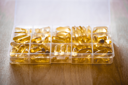 permeability: Omega 3-6-9 fish oil yellow softgels into daily pill box on wooden board. Backlit detail of fat acid tablets.