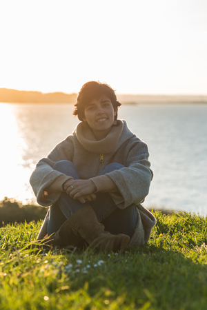 Young woman sitting outdoor enjoying sunset with sea sight. backlit portrait of heatlhy successful woman.