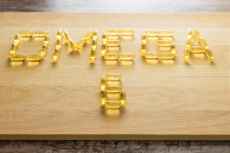 permeability: Omega 3-6-9 fish oil yellow softgels drawing omega 6 letters on wooden board on rustic table. Stock Photo