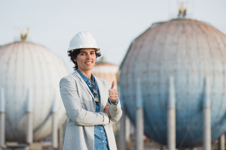 preasure: successful independent engineer smiling woman on industrial area with safety helmet crossing arms. Pioneer woman at work with spherical tanks giving thumb up.