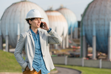 preasure: successful independent engineer smiling woman talking on the phone on industrial area with safety helmet. Pioneer woman at work with spherical tanks.