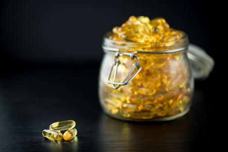 permeability: Omega 3-6-9 fish oil yellow softgels on wooden black board into airtight glass jar Stock Photo