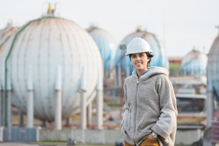 preasure: successful independent engineer smiling woman on industrial area with safety helmet looking to the camera. Pioneer woman at work with spherical tanks.