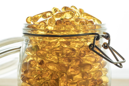 airtight: Omega 3-6-9 fish oil yellow softgels into airtight glass jar Stock Photo