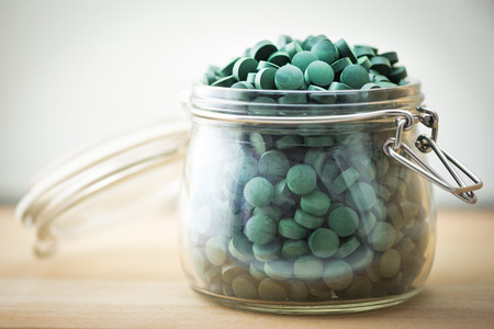 antioxidant: Spirulina supplement pills into airtight jar. Antioxidant alga nutrition.